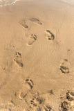 Huellas en la arena en la puesta del sol Fotografía de archivo libre de regalías