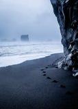 Huellas en la arena negra, playa islandesa Fotografía de archivo libre de regalías