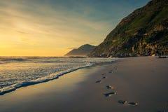 Huellas en la arena en la puesta del sol foto de archivo