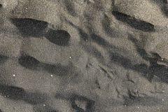 Huellas en la arena volcánica negra de la isla española de Tenerife Fotos de archivo