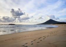 Huellas en la playa a la colina foto de archivo