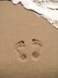 Huellas en la playa de la arena Imagenes de archivo