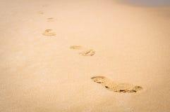 Huellas en la playa de la arena Foto de archivo libre de regalías