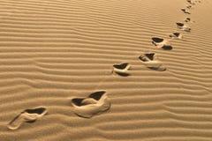 Huellas en las dunas de arena Cadena de huellas descalzas en la arena Huellas humanas en fondo de la arena Pasos del pie que se v Fotografía de archivo
