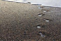 Huellas mojadas en playa de la tabla Foto de archivo