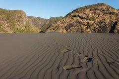 Huellas a través de la duna de arena negra Imagen de archivo libre de regalías