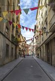 Street festival with colorful pennants on ropes hanging on facades of old houses in the center of Huesca city. HUESCA, SPAIN - SEPTEMBER 26, 2015: Street Royalty Free Stock Images