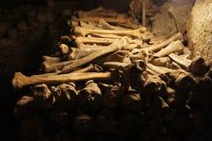 Huesos apilados contra la pared en las catacumbas debajo de París Fotos de archivo libres de regalías