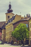 The Huet Square, Sibiu, Romania. Sibiu, Romania - 06 May, 2015: The City Hall and the Roman-Catholic Church tower as seen in the Huet Square, one of the three Stock Photos