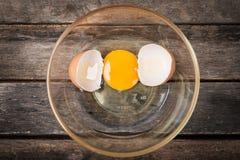 Huevo agrietado del pollo con la cáscara de la yema de huevo y de huevo en el plato, fondo de madera Fotos de archivo