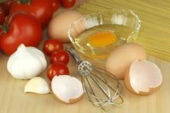 Huevo, ajo, tomate y pastas Imagenes de archivo