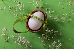 Huevo blanco en cesta en fondo verde con las flores imagenes de archivo