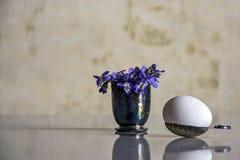 Huevo blanco en una cuchara de plata y un ramo de flores del bosque foto de archivo