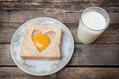 Huevo con el fondo de madera del pan entero del grano Imagen de archivo