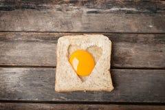 Huevo con el fondo de madera del pan entero del grano Foto de archivo