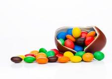 Huevo de chocolate con los pequeños caramelos redondos coloridos Imágenes de archivo libres de regalías