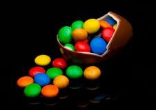 Huevo de chocolate con los pequeños caramelos redondos coloridos Imagen de archivo