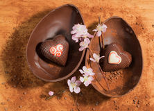 Huevo de chocolate de Pascua con una sorpresa de dos corazones adornados, asperjada con el polvo de cacao y el flor de la almendr Imagenes de archivo