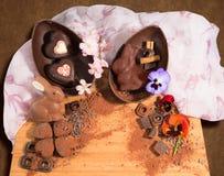 Huevo de chocolate de Pascua con una sorpresa de dos corazones adornados y de un conejo de pascua, asperjada con las flores del p Imagen de archivo libre de regalías