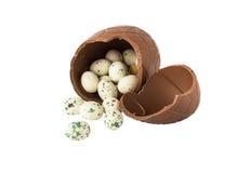 Huevo de chocolate quebrado con los pequeños huevos de caramelo aislados en blanco fotos de archivo