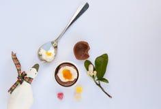 Huevo de Cholocate Pascua al lado de la cuchara con la yema de huevo, la cáscara de huevo y el caramelo Fotos de archivo