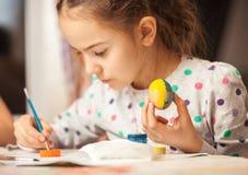 Huevo de la pintura de la niña en el cristiano pascua Foto de archivo