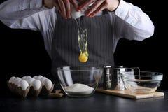 Huevo de la rotura del hombre en cuenco receta de la empanada que hace en fondo oscuro fotografía de archivo