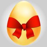 Huevo de oro con el arqueamiento rojo Imagen de archivo