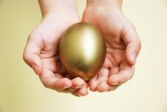 Huevo de oro en manos Foto de archivo