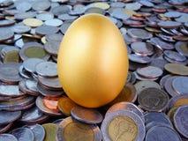 Huevo de oro en monedas Fotos de archivo