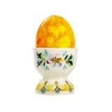 Huevo de Pascua amarillo en un tenedor de la porcelana aislado en el fondo blanco Imagen de archivo libre de regalías