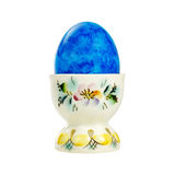 Huevo de Pascua azul en un tenedor de la porcelana aislado en el fondo blanco Fotos de archivo