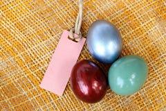 Huevo de Pascua colorido en el fondo de bambú de la armadura con la etiqueta de papel Fotografía de archivo