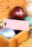 Huevo de Pascua colorido en la caja de madera con la etiqueta de papel Fotos de archivo