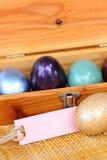 Huevo de Pascua colorido en la caja de madera con la etiqueta de papel Foto de archivo