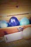 Huevo de Pascua colorido en la caja de madera con la etiqueta de papel, Fotografía de archivo libre de regalías