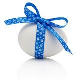 Huevo de Pascua con el arco azul festivo aislado en el fondo blanco Imagen de archivo libre de regalías