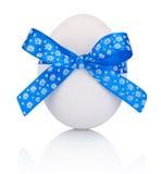 Huevo de Pascua con el arco azul festivo aislado en el fondo blanco Fotos de archivo libres de regalías