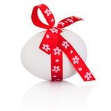 Huevo de Pascua con el arco rojo festivo aislado en el fondo blanco fotos de archivo libres de regalías