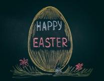 Huevo de Pascua con la frase Pascua feliz en la pizarra Imagen de archivo libre de regalías