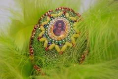 Huevo de Pascua con la imagen de Jesús en plumas Imágenes de archivo libres de regalías