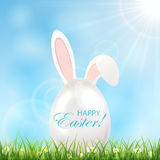 Huevo de Pascua con los oídos en una hierba