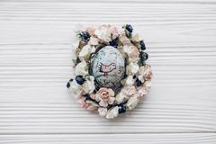 Huevo de Pascua con los ornamentos del polluelo en jerarquía floral con las flores en r Imágenes de archivo libres de regalías