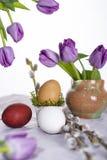Huevo de Pascua con los tulipanes y la ramita del sauce Fotos de archivo