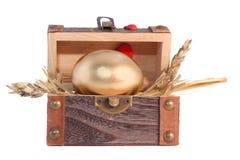 Huevo de Pascua de oro en el rectángulo de regalo de madera Imagen de archivo