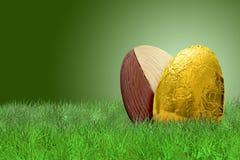 Huevo de Pascua de oro en hierba en fondo verde Foto de archivo libre de regalías