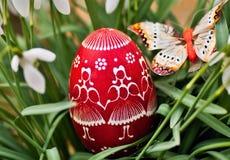 Huevo de Pascua decorativo rojo en césped Imágenes de archivo libres de regalías