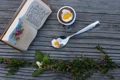 Huevo de Pascua del chocolate, cuchara con la yema de huevo y libro de oración en el cortejar Foto de archivo