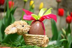 Huevo de Pascua del chocolate en el jardín de la primavera Fotos de archivo