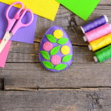 Huevo de Pascua del fieltro adornado con las hojas del verde y las flores coloridas Fotografía de archivo
